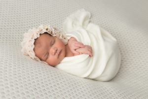 newborn girl swaddled in white with bonnet in studio session